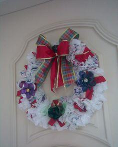 Guirlanda feita com sacos plásticos e papelão grosso tendo 30 cm de diâmetro. Laços de fitas decorativas, flores e laço de pet. R$50,00