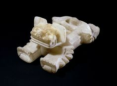 Offering vessel made of tecalli (in this case calcite onyx), in the form of an ocelot. The eyes and mouth of the vessel were probably once inlaid with semi precious shell or stone and the two depressions hollowed in the back were used to place offerings.       Teotihuacan 400-600 (circa).