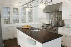 Beautiful crisp, clean traditional kitchen design - dark island surface by Venegas and Company