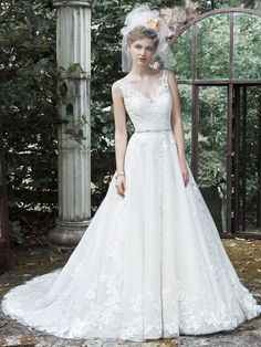 Maggie Sottero - SYBIL Antique Ivory Size 22 and Ivory Size 10 This exquisite ball gown wedding dress is complete with floral lace appliques drifting down a tulle skirt, an elegant illusion V-neckline, and a glittering Swarovski crystal belt. Finished with plunging V-back and crystal buttons over zipper closure.