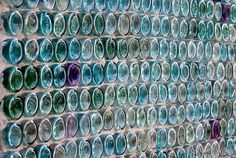 I want a glass bottle wall.So neat!!They are really beautiful when the sun shines through too. Use with the backyard kitchen and fireplace