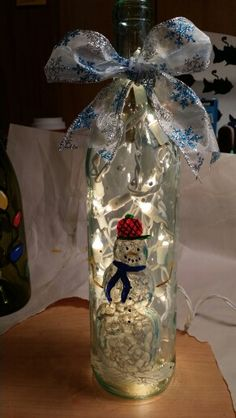 Snowman painted on wine bottle.