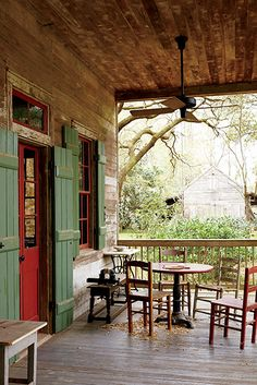The forty-two-foot-wide front porch, complete with ceiling fans and green hurricane shutters. #SouthernHomes #creolecottage #gardenandgun Photo Credit: Brie Williams.