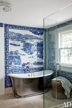 A bath in Shelter Island, New York, sports a mural by Chelsea Arts Tile + Stone; the tub is by Waterworks, with fittings by Leroy Brooks | archdigest.com