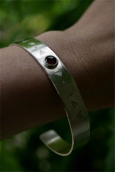 Sterling bangle with punch decoration and garnet