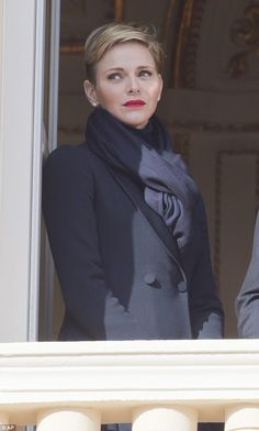 Charlene was seen looking out from the balcony in a black scarf and tailored suit, she wore a scarlet lipstick to give her ensemble a pop of colour