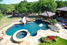 like the layout of this pool with the hot tub, tanning ledge, slide and rock wall, and the covered outdoor kitchen