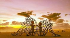 """One of the most powerful art pieces at Burning Man this year. """"Love"""" by Ukrainian sculptor Alexander Milov  . Milov created the sculpture and fondly titled it 'Love.' The sculpture includes two huge wire-frame adults seated back to back, each with an inner child trapped inside reaching out to the other.   Looking at the piece of art provokes a different feeling for all."""