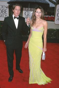 "At the decidedly damp 57th installment of the Golden Globe Awards, Denzel Washington may have won for his role in ""The Hurricane,"" but ""Notting Hill's"" Hugh Grant arrived with the evening's most brilliant ray of canary yellow sunshine, Elizabeth Hurley. While not built to last, this was one couple that knew how to work an umbrella as well as a serious British pout."
