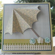 """1. Cut a 6"""" circle in half. Fold the half circle in half and then half again.  2. Fold each one of those sections in half.  3. Using a small circle punch, cut a small scallop out of each section.  4. Paint a coffee stirer with a silver paint pen.  5. Put together background layers. (5"""" x 5"""") Adhere to a 5 1/2"""" x 5 1/2"""" card.  6. Fold back the end two sections of the umbrella, trim as needed and adhere to front of card.  7. Apply a little bit of glue to the back of the silver stick and glue…"""