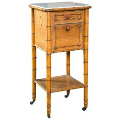 A French faux bamboo nightstand or commode of pine featuring a white marble top over a frieze with drawers and cabinet fall.