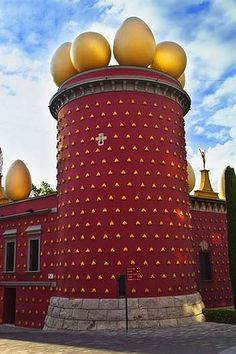 Dali Theatre-Museum. In 1960, the artist bought the Municipal Theatre, a building that had been destroyed by fire at the end of the Spanish Civil War in 1939, turning it into the largest surrealist object in the world. First he painted the building maroon and stuck loaves of bread to the walls (they are made from plaster). He positioned giant eggs along the rampart and planted cypress trees out front.