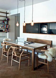 En el otro extremo del ambiente y contiguo a la cocina que se abre hacia este espacio con una gran raja horizontal a modo de pasaplatos, el comedor reúne una mesa con estructura de petiribí macizo y tapa de mármol de Carrara.