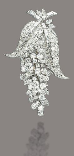 A DIAMOND BROOCH, BY MARCHAK. The brilliant-cut and marquise-shaped diamond flexible wisteria flower surmounted by pavé-set diamond leaves with baguette-cut diamond stems, 1960s, 6.2 cm, with French assay marks for platinum and gold. Signed Marchak Paris, no. 4755. #GoldBrooches #goldbroochesfordresses