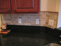 This tile backsplash gives contrast to the black granite countertop and the rich cherry cabinets.