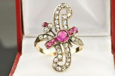 Victorian Ring, circa 1880's, with it's unusual design and bright red rubies - very striking!! Holding 5 old mine cut and 1 center cabochon cut rubies