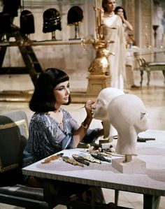Cleopatra gets crafty!  Elizabeth Taylor takes a break on the set of the epic film.