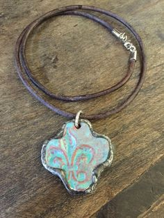 A beautiful handmade ceramic soldered Fleur de Lis cross pendant is accented with a 3mm distressed leather cord necklace. Perfect layering