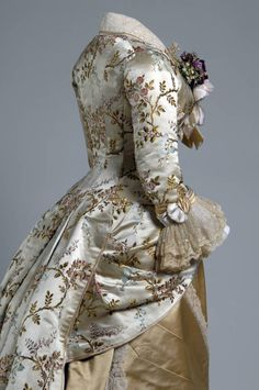 Dinner dress, 1878. Silk brocade, lace, silk satin. Emile Pingat, France. | Dress of off-white silk brocaded in a multicolored floral and vine motif. Polonaise has modified V-shaped neckline and three-quarter length sleeves, both of which are trimmed with gold-colored satin and white satin piping. Blonde lace at collar and cuffs. Skirt of gold-colored satin. Triangular pattern pieces trimmed with lace meet at front, offering a sunburst effect at center front hem.