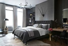 Masculine bedroom features walls clad in dark grey grasscloth wallpaper accented with antlers over ...