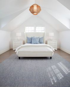 clean white bed frame with higher and wider headboard a couple of bedside tables in white accent blue pillows textured blue area rug white walls white pointed ceilings of Complete Your Bedroom Needs with Dillards Bedroom Furniture Sets