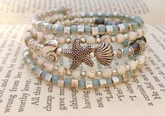 A 5 coil memory wire wrap bracelet featuring smooth 3mm smooth creamy Howlite beads, 3mm seafoam green/blue glass seed beads and 6mm hematite beads. Accented with a variety of Tibetan silver spacer beads. The focal of this bracelet is a Tibetan silver starfish, snail shell, and clam shell cluster in the center of the coils. Finished with a wire wrapped 6mm hematite bead on each end. Made with stainless steel memory wire and will fit most teen/adult sized wrists.  On the medium side in…