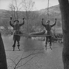 Members of 298 Field Ambulance Company, Royal Army Medical Corps, demonstrate a method of carrying a stretcher case across a river using a rope bridge at Grasmere in the Lake District, 18 November 1943.