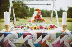 Cake table full of zinnias and covered in a quilt @myweddingdotcom