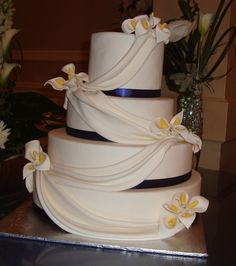 Wedding cake with Calla lilies, fondant swags and blue ribbon ...
