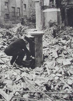 WWII (c.1941) A postman emptying the pillar box the morning after a heavy bombing raid in London.
