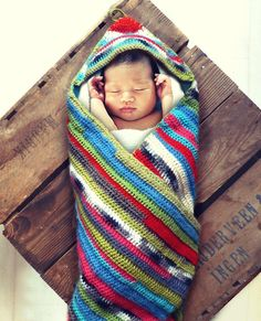 Crocheted hooded striped baby blanket.  via Etsy.  I like it!  Looks like an American Indian or Mexican blanket.