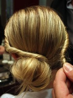 Pinner says: Before you put your hair in a bun, leave two long strands of hair out on the sides at the front. once hair is in a bun, twist/braid the strands and wrap around the bun. pin them with bobbies or clips.