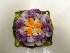 Flor de crochê confeccionada em barbante multicolorido amarelo, lilás e verde. R$ 5,75