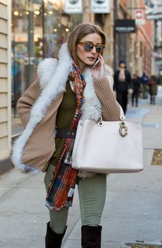 Olivia Palermo manages to master Fall layering with a vest, scarf, and chunky knit.