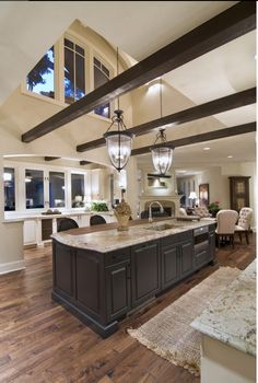 I just like the beams and the floors...The chandeliers look dumb, and the furniture is a little hoity. Although, the cabinets look super-functional.... And is that a drawered dw? WTH is that appliance?