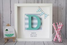 White wooden box frame with a decorative paper background, miniature wooden bunting and a wooden, hand painted letter of your choice which is 12cm tall and 2cm thick. Can be personalised with name, date of birth and birth weight underneath with small white cubed letters. The beautiful
