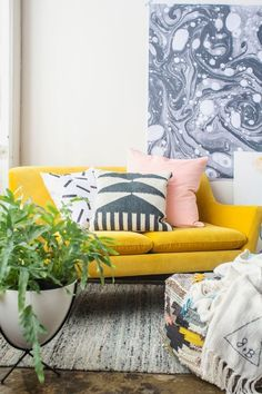 Bright yellow couch pops against the greys in this room.