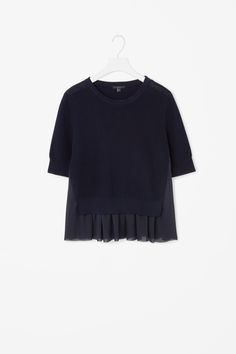This top is made from a knitted cotton with a ribbed finish and a sheer ruche skirt detail. A close fit, it has short sleeves, round neckline and tightly knitted finishes.