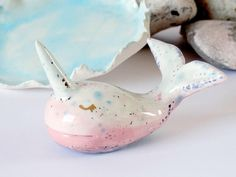Narwhal Ring Cone - Ring Dish - Ring Holder ........................................................................... This little narwhal ring holder and trinket dish set have each been individually hand sculpted from earthenware clay. Each component is unique, The narwhal in this set has been glazed in mostly pink tones with some blue feature areas. It also has hand applied 22kt gold lustre features including lustre eyes. The tail area has been lightly glazed with mother of pearl for a…