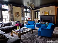 In the family room, custom chairs and an ottoman are covered in a deep sky-blue fabric from Designers Guild. Sofa fabric, Old World Weavers. Lee Jofa curtains and Schumacher grass cloth on the walls. Vintage coffee table. Antelope-print carpet, Stark. Chandelier, Jonathan Adler. Ceiling and trim, Benjamin Moore's Black Panther.