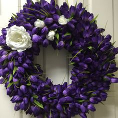 My daughter's Easter Memorial wreath.  Purple as the color of the king, and white roses to represent the resurrection.  The large rose represents her life and the three rose buds for her three boys who live in heaven.  Created by Twentycoats Wreath Creations (2015)