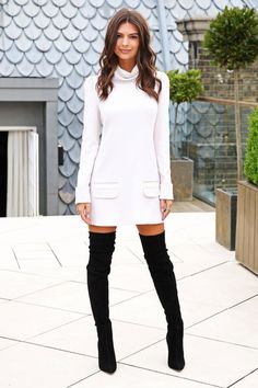Emily Ratajkowski in a white turtleneck mini dress and black suede thigh-high boots