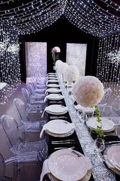 Décoration réalisée avec du ruban de strass argent, des chaises transparentes, de grosses boules de fleurs blanches, et des guirlandes de loupiotes Décor de table composé d'une caisse en bois…