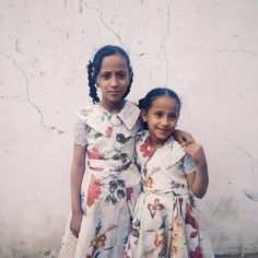 Yemeni sisters pose for a portrait outside their home that was hit by an air strike in Sanaa, Yemen. (Photo by Alex Potter)  #yemen #sanaa #middleeast #ramadan #arabia #sisters #family #dressup #braids #flowers #youth