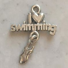 """This adorable charm is approximately 5/8"""" wide by 1"""" long. It has a swim suit toggle dangling down from the proclamation that I Love Swimming!"""