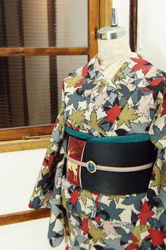 ベージュの地に重なりあう楓の葉が織り出された御召の袷着物です。