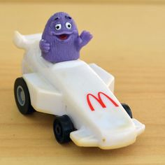 "Vintage McDonalds Grimace Race Car Happy Meal Toy.    This is Grimace in a Formula One style white car with the McDonalds ""Golden Arches"" logo in the front. You can pull it back on a surface and it will go!    This toy is in good vintage condition with some yellowing from age. Some plastics are prone to this due to the manufacturing process.    The bottom states: -GRIMACE-McDONALDS CORP. 1988-P.c.-CHINA-    The car is about 2.5"" long and 1.5"" tall."