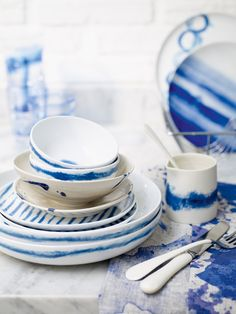 Designers Guild Jinishi porcelain pasta bowls, £13 each, tea plates, £7 each, cereal bowls, £8 each and side plate (far back), £8 all from Amara; Cream with blue saucer, £48 (including cup), cream with blue bowl, £28 and Blue Bohemia runner, £78 all from Anthropologie; Small tie dye jug, £28 from Ali Tomlin; Enamel dipped cutlery, £37.50 for a four-piece set from Toast; Harbour side plate (near back), £4.50 from Bhs; Cirro tumblers, £45 for a set of four from LSA.