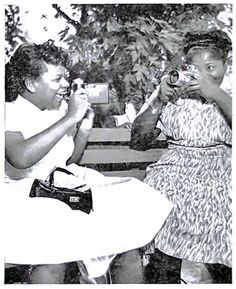 """""""From Old Time Radio Bulletin: """"Taking careful aim at each other with their cameras, TV spelling whiz kid Gloria Lockerman and gospel singer Mahalia Jackson get snapshots for their personal collection..."""