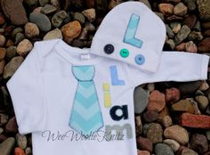 Newborn Baby boy outfit personalized with name and chevron tie applique and beanie hat. An adorable and unique coming home outfit. I can do this design on a gown or bodysuit.  This is a think and cushy infant gown with elastic at the bottom making for quick diaper changes and a happy baby!   My appliques are hand cut and sewn on using a regular sewing machine, so no two outfits or items will turn out exactly the same.  Letter placement and fabrics may differ slightly due to length of name…